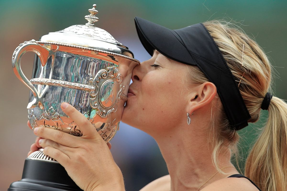 In this June 9, 2012, file photo, Maria Sharapova of Russia holds the trophy after winning the women's final match against Sara Errani of Italy at the French Open tennis tournament at Roland Garros stadium in Paris.