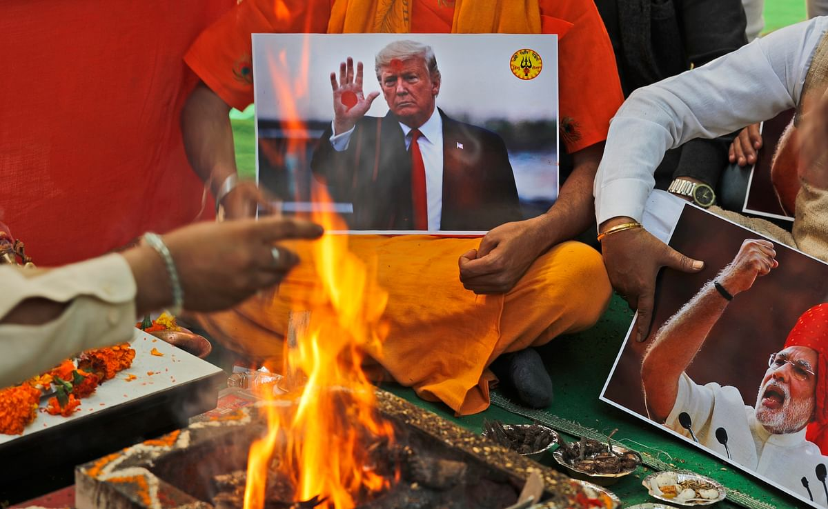 A Hindu priest offers prayers holding portraits of Indian Prime Minister Narendra Modi and U.S. President Donald Trump in New Delhi, India. The prayer event was held by Hindu Sena for a successful Trump win.