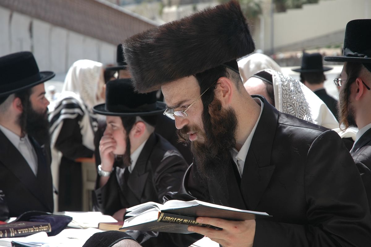 Jews reading the Torah at the Western Wall.