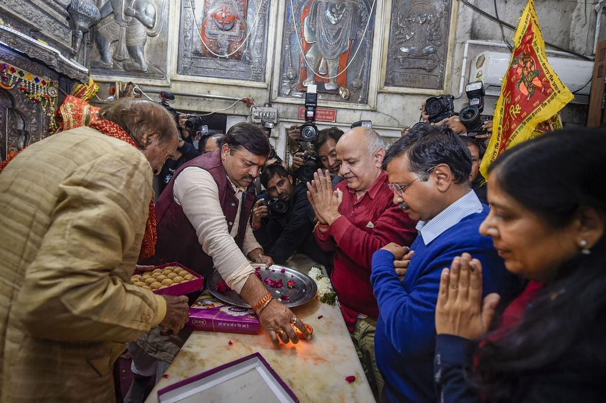 Delhi CM and AAP convenor Arvind Kejriwal (C), accompanied by wife Sunita, Dy CM Manish Sisodia and other party leaders, offer prayers at the Hanuman Mandir in Connaught Place on Tuesday, 11 February 2020.