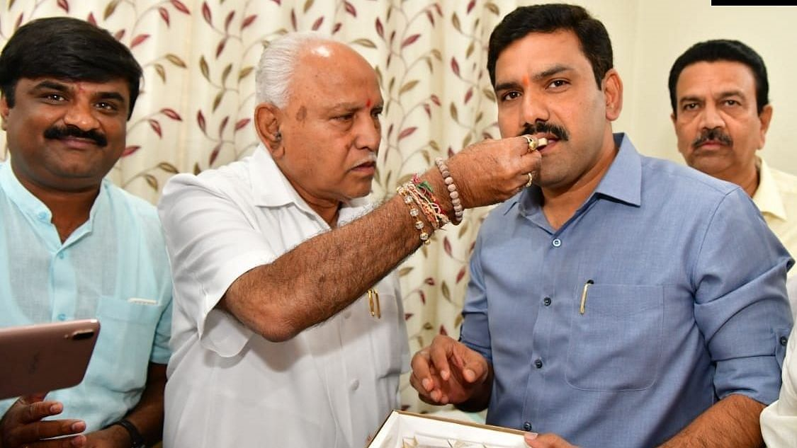 Karnataka Chief Minister BS Yediyurappa celebrates with his son BY Vijayendra.