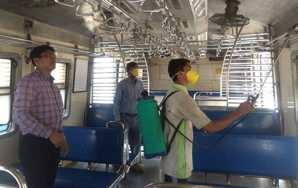 Sunil Kumar Bairwa supervises a cleaner sanitising a train coach.