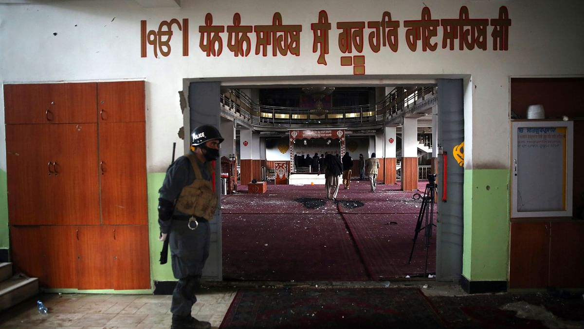 File photo: An Afghan policeman stands guard at the entrance of the gurudwara after the attack.