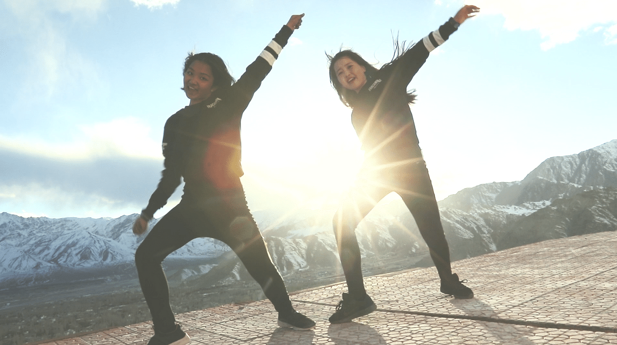 Two girls dance in the backdrop of snow-capped mountains.
