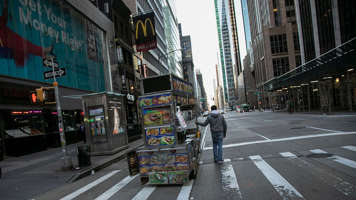 A food truck vendor pushes his cart down an empty street near Times Square in New York, on Sunday, 15 March 2020.