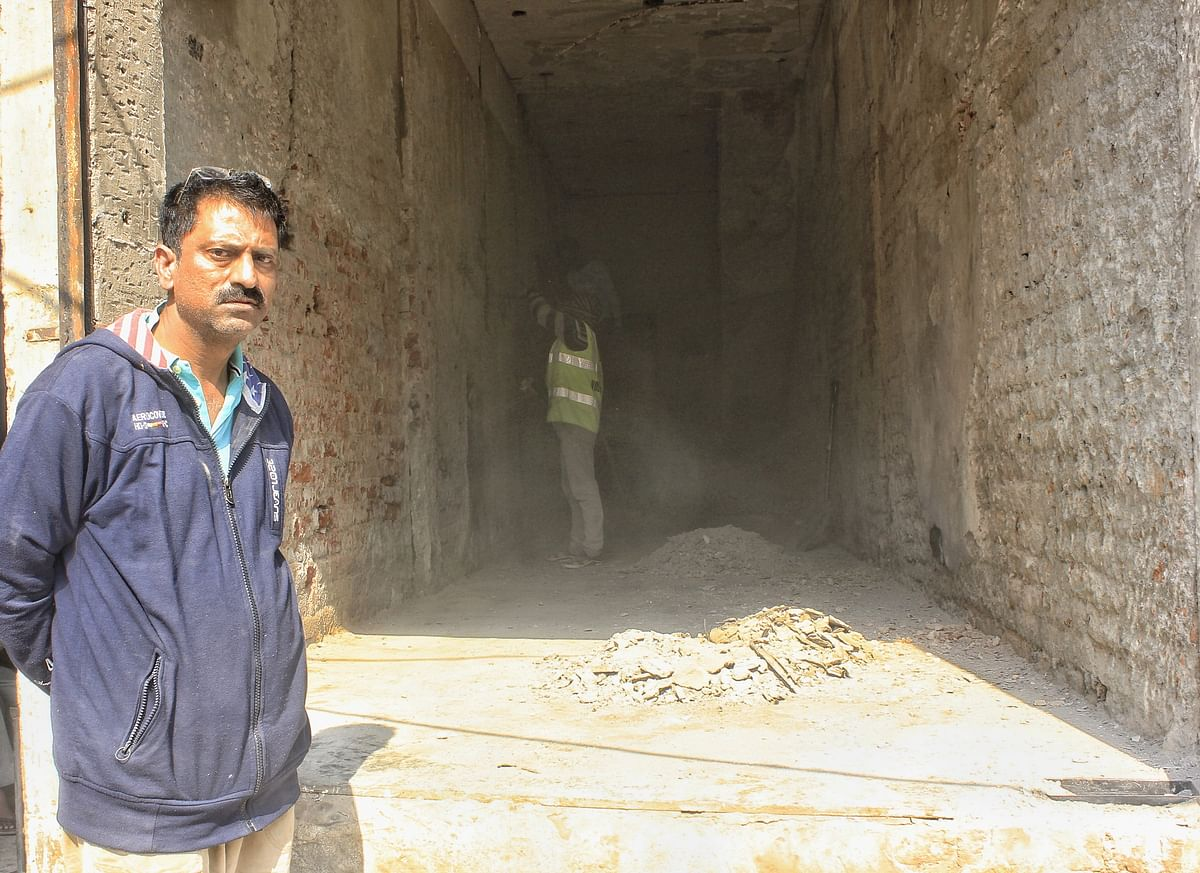 Yousuf stands along side his medical store being reconstructed