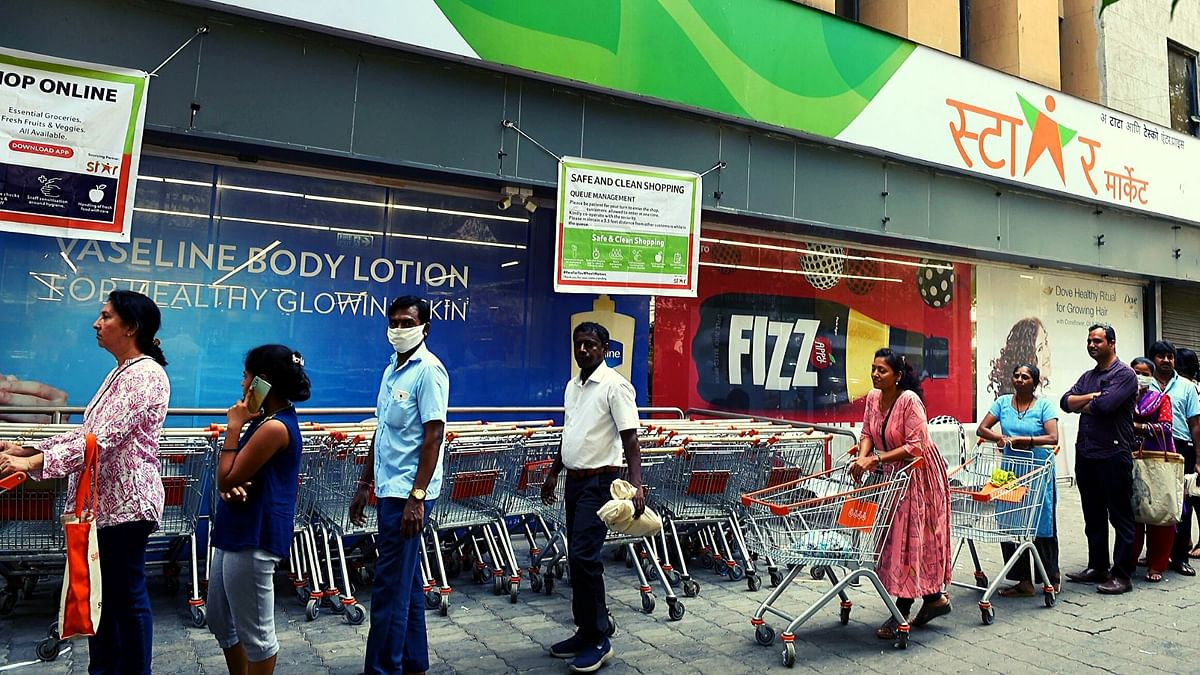 A file image of people wearing face masks in the wake of coronavirus pandemic standing in a queue to buy groceries, at Churchgate in Mumbai.