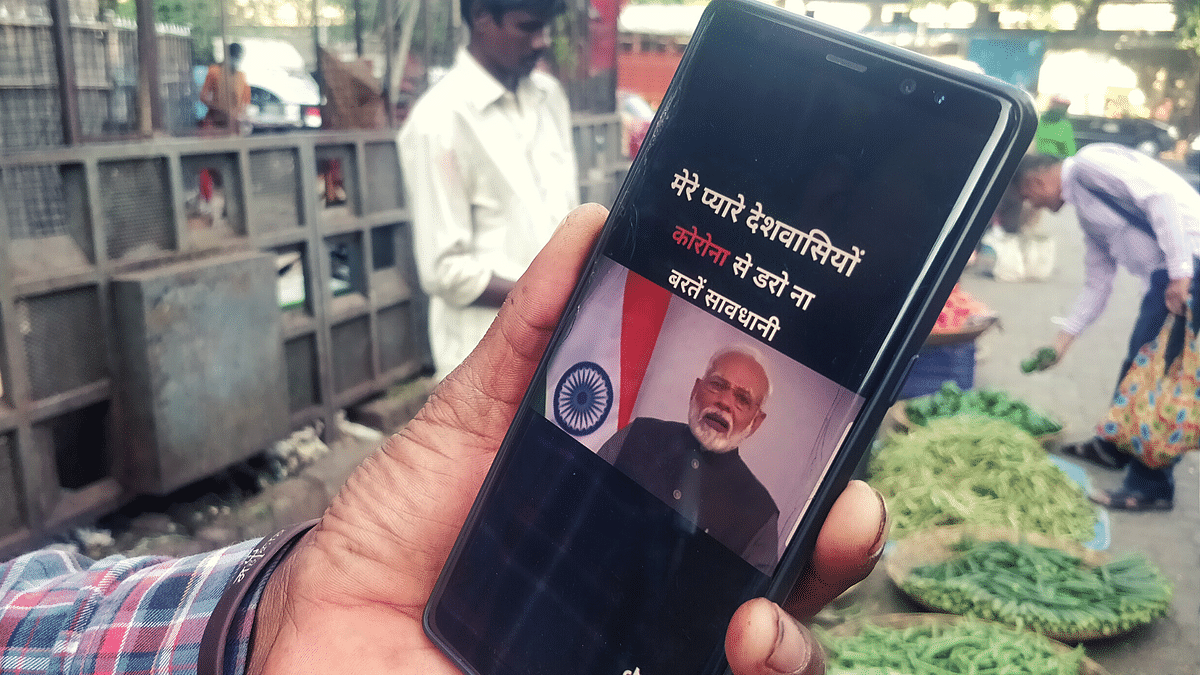 Monu shows a video on his mobile phone, of Prime Minister Modi speaking about coronavirus.