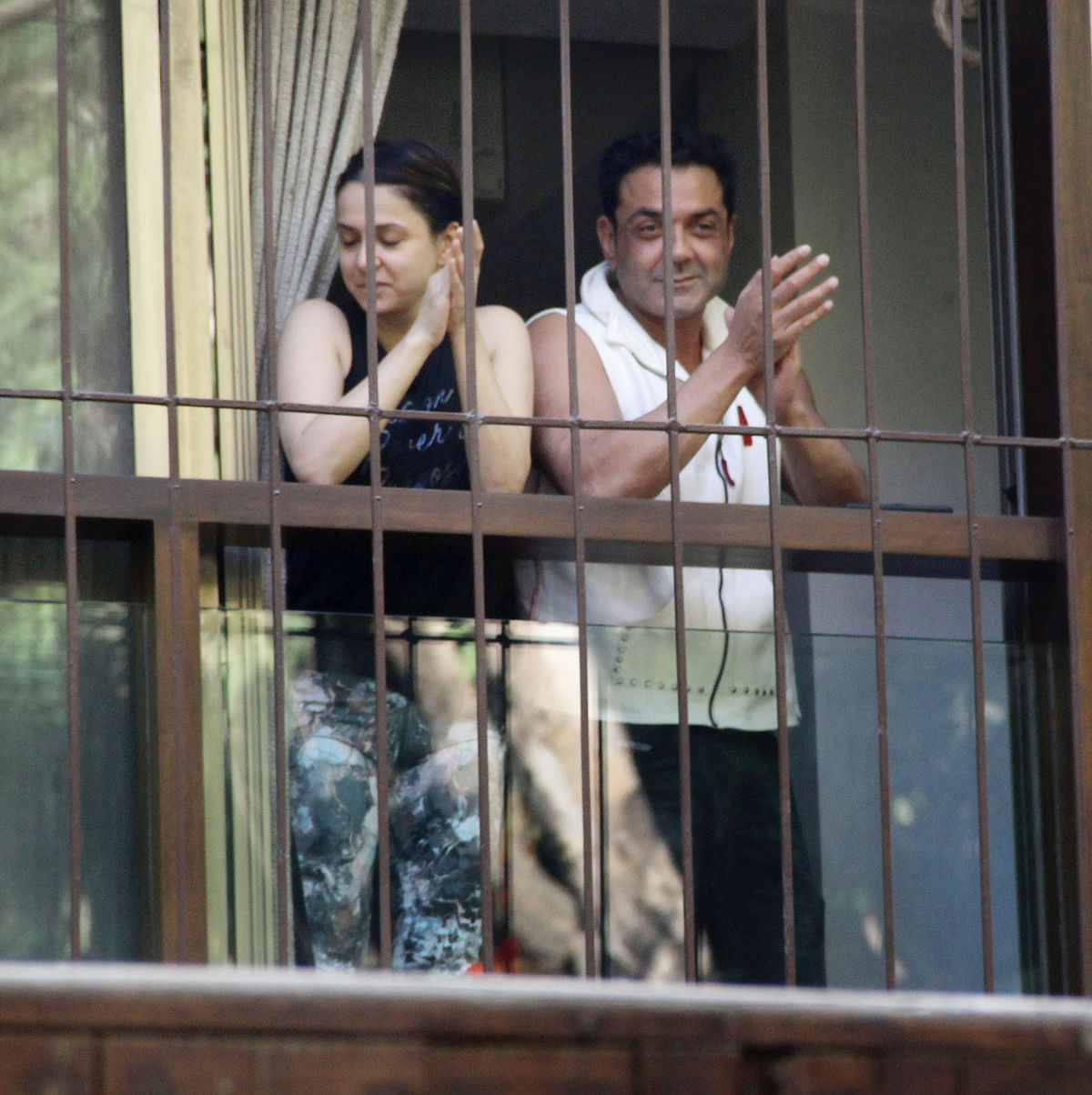 Bobby Deol claps with the crowd.