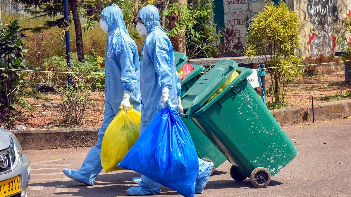 Medical staff, wearing protective suits, hold medical waste as they exit the Special Isolation Ward set up to provide treatment to novel coronavirus patients at Kochi Medical college, in Kerala.