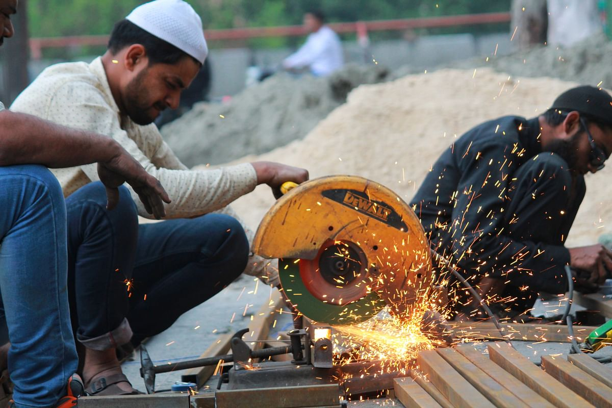 Workers at the Gokulpuri Tyre Market working on the reconstruction of Abdullah Bukhari Mosque.