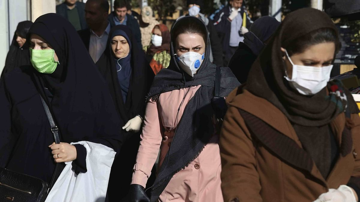 People wearing face masks walk on a sidewalk in Tehran, Iran.