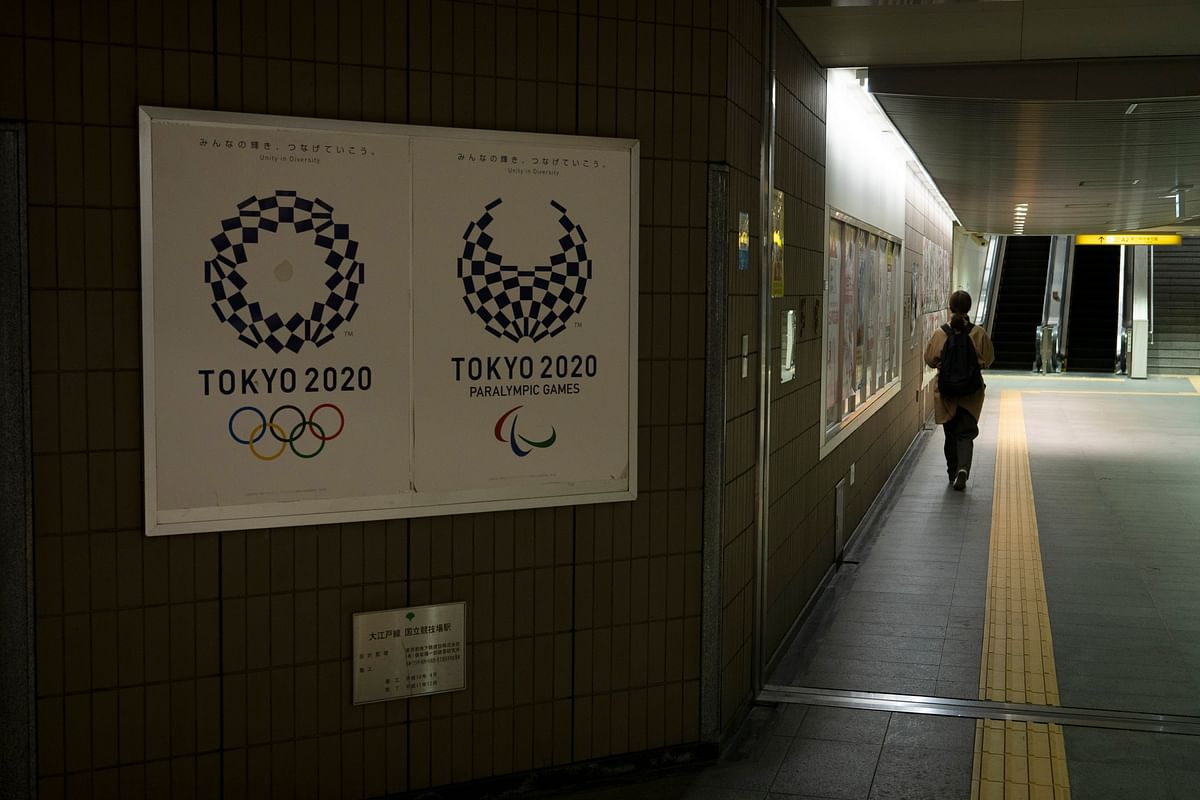 A commuter leaves a train station adorned with posters promoting the Tokyo 2020 Olympics in Tokyo, Monday, March 23, 2020.