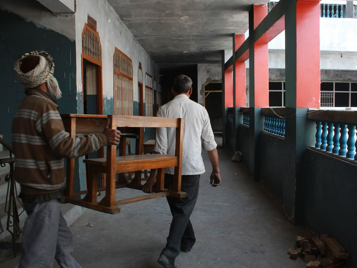 Desks being arranged into classes that have been reconstructed.