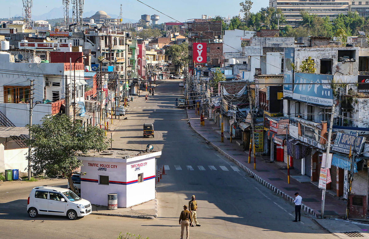 Security personnel wearing protective face mask stand guard on a deserted city street in Jammu.