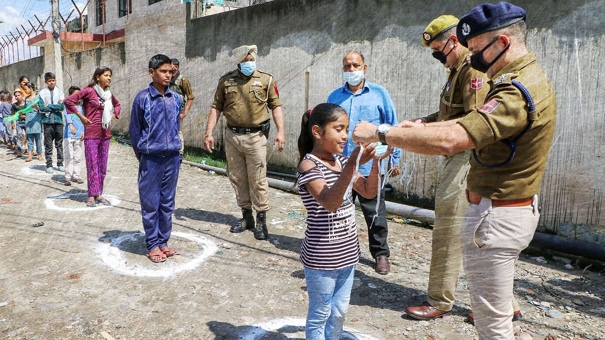Police distribute masks among people during a nationwide lockdown, in Jammu, Saturday.