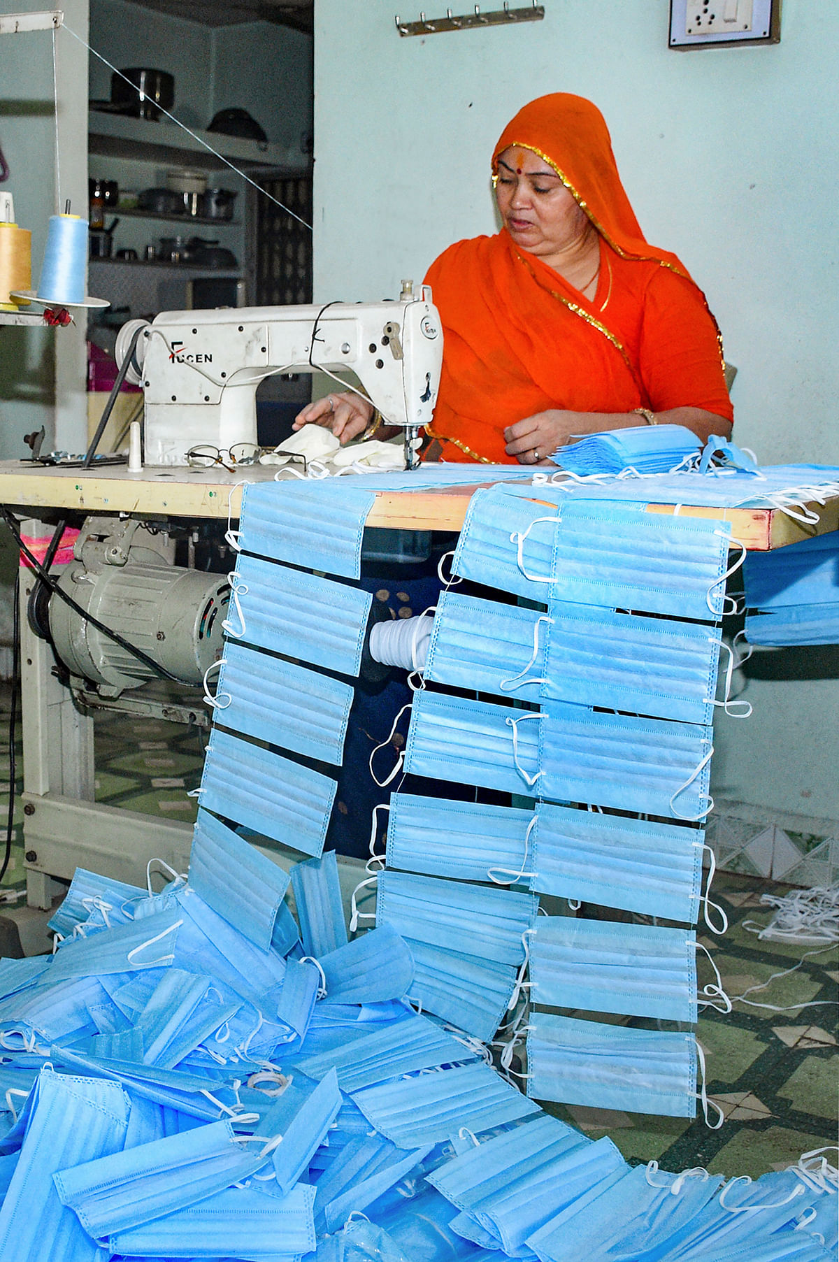 A worker stitches masks at a manufacturing unit as demand for face masks has increased in wake of COVID-19 pandemic, in Surat, Tuesday, 17 March 2020.