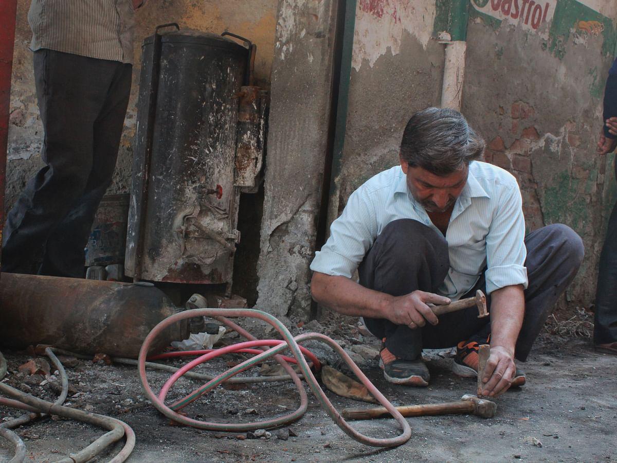 Mansoor fixes his tool from what is left of his welding shop.