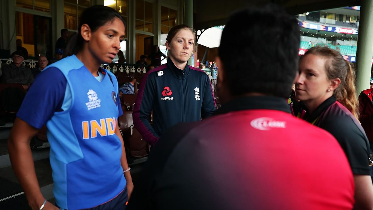 Captains Harmanpreet Kaur of India and Heather Knight of England speak to umpires before play was abandoned due to rain during the ICC Women's T20 Cricket World Cup Semi Final.