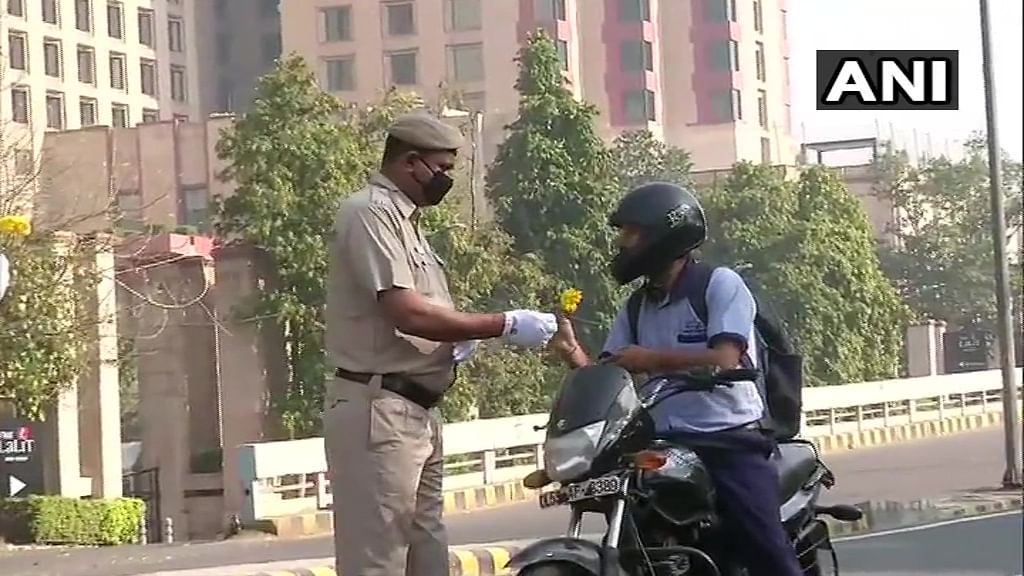 Delhi: Police personnel near Barakhamba Road offer flowers to the locals out on roads, requesting them to stay at home and observe the countrywide curfew.
