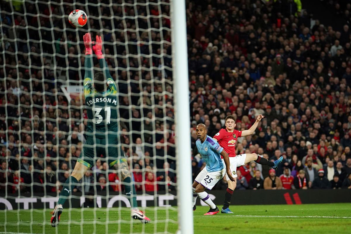 Manchester United's Daniel James, right, shoots, as Manchester City's goalkeeper Ederson, left, makes a save during the English Premier League soccer match between Manchester United and Manchester City at Old Trafford in Manchester.