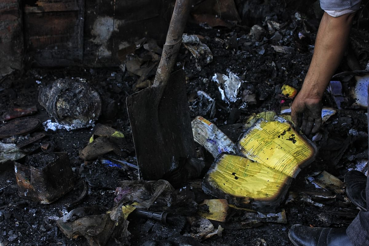 Mukesh finds his accounts ledger half burnt from the rubble.