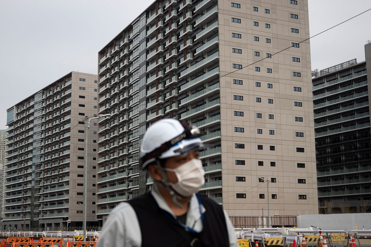 A worker walks through the athletes' village for the Tokyo 2020 Olympics, in Tokyo, Monday, 23 March 2020.