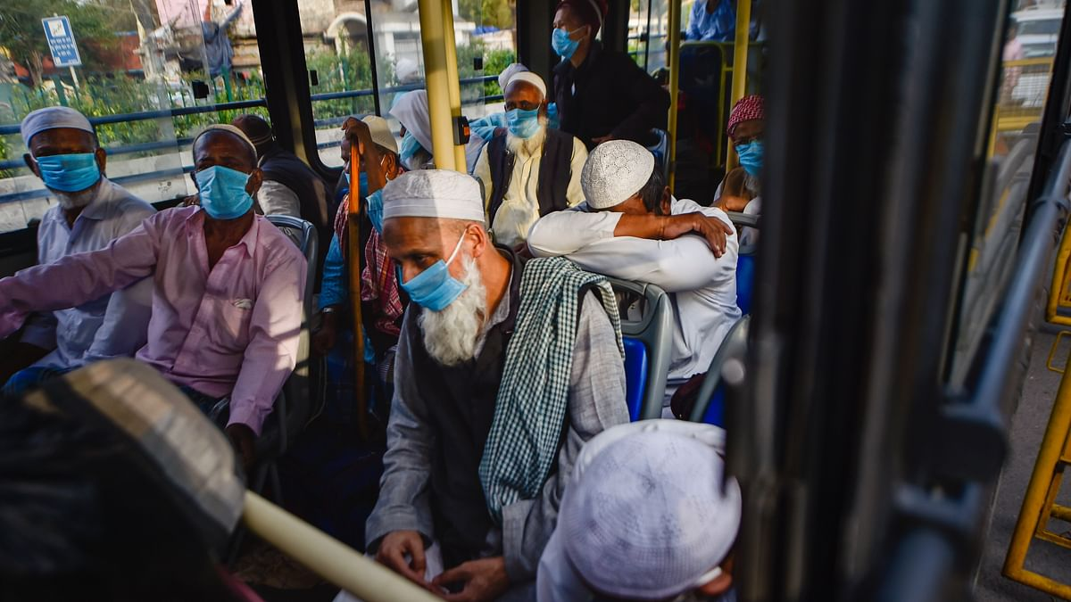 People wearing masks leave for hospital in a bus from Nizamuddin area, after several people showed symptoms of coronavirus following taking part in a religious gathering a few days ago, during the nationwide lockdown, in New Delhi, Monday, 30 March.