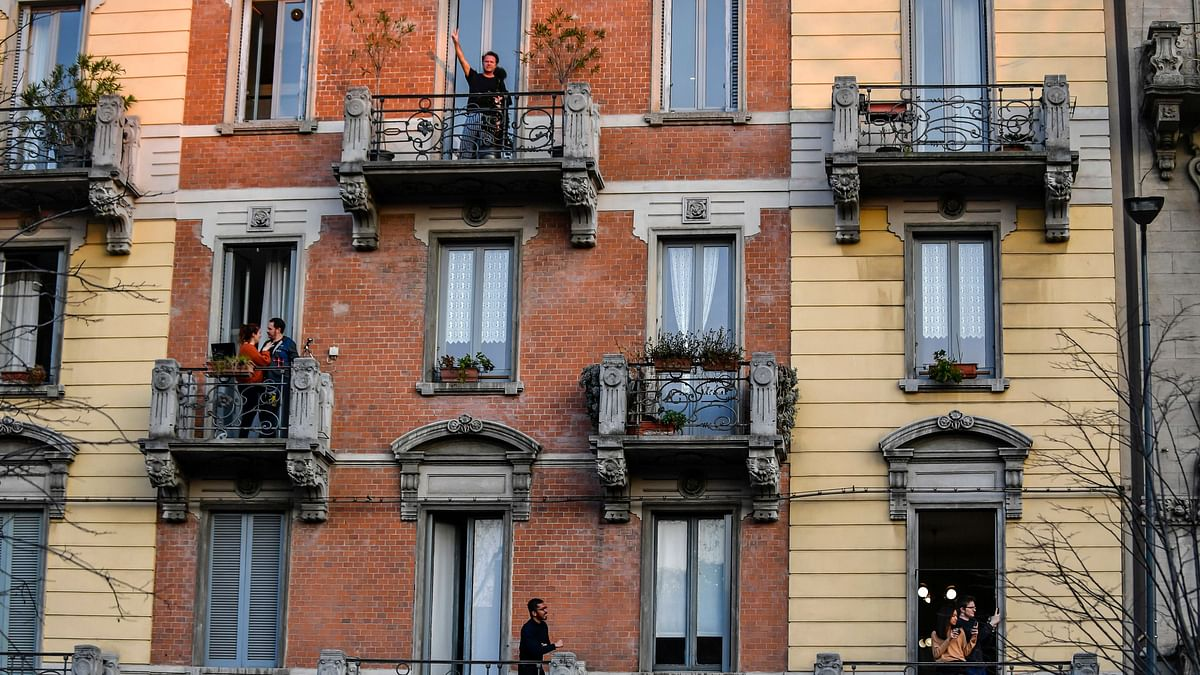 People stand on their balconies during one of the many flash mobs taking place these days in Milan, Italy, Sunday, 15 March 2020.