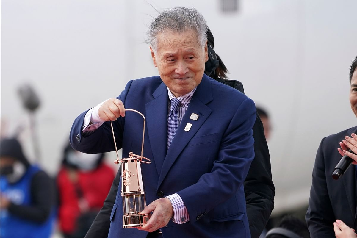 In this March 20, 2020, file photo, Tokyo 2020 Olympics chief Yoshiro Mori carries the Olympic flame during the Flame Arrival Ceremony at Japan Air Self-Defense Force Matsushima Base in Higashimatsushima.