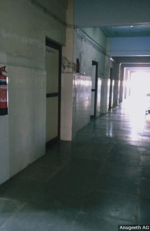 The corridor leading to isolation rooms in Pathanamthitta's General Hospital. The windows in the ward are open to allow in fresh air, the only view of the world outside for the patients and the staff.