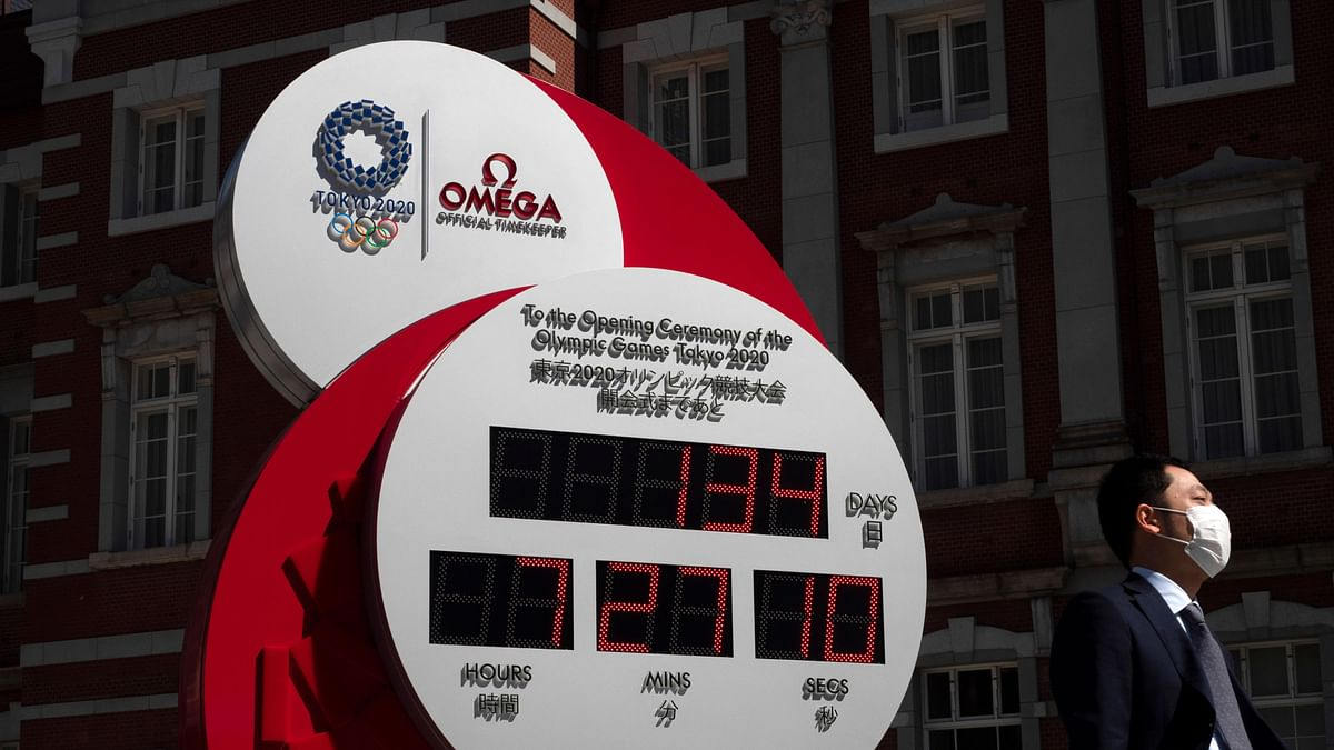 A man with a mask walks past a countdown clock for the Tokyo 2020 Olympics Thursday, 11 March.
