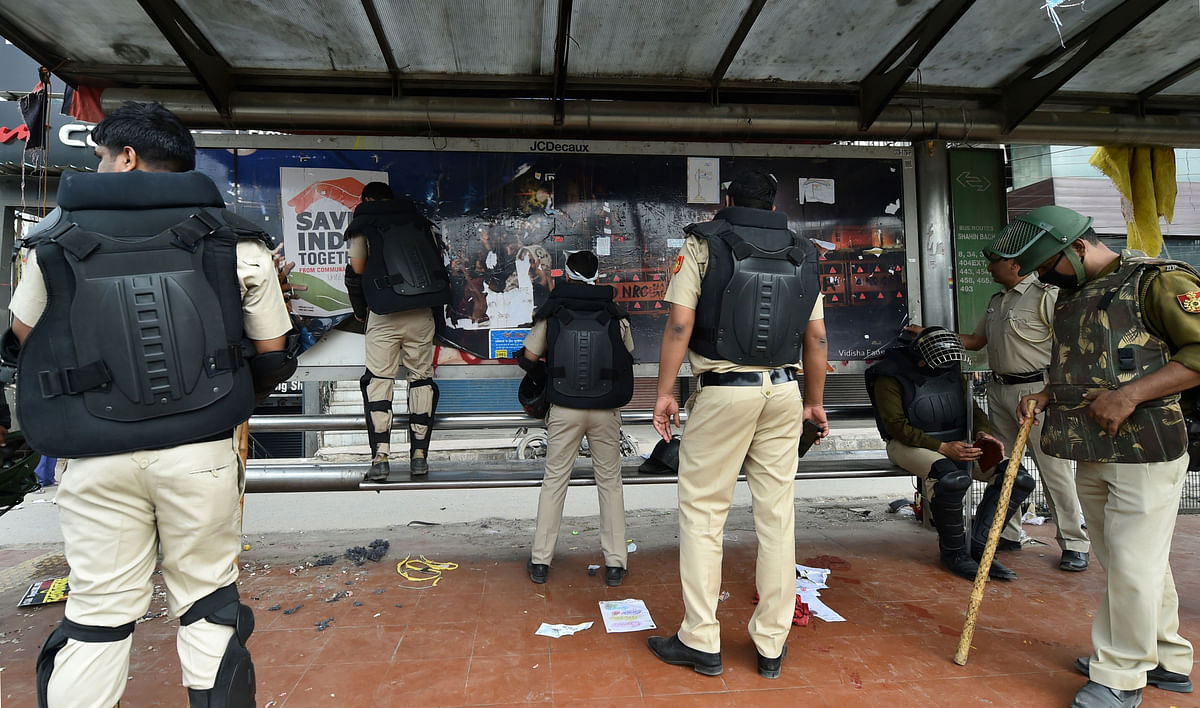 Delhi Police personnel remove posters at Shaheen Bagh protest site.