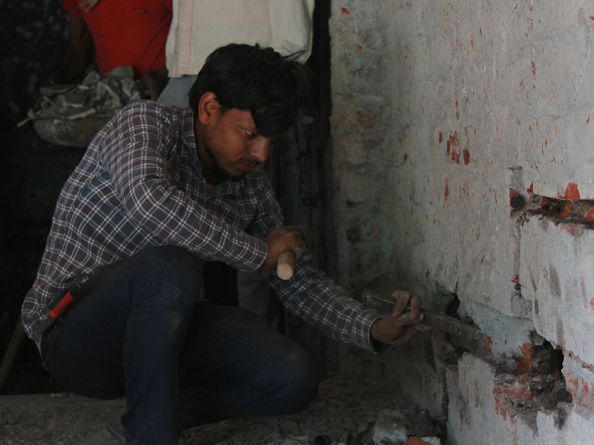 A worker chips a wall in Dulichand's shop.