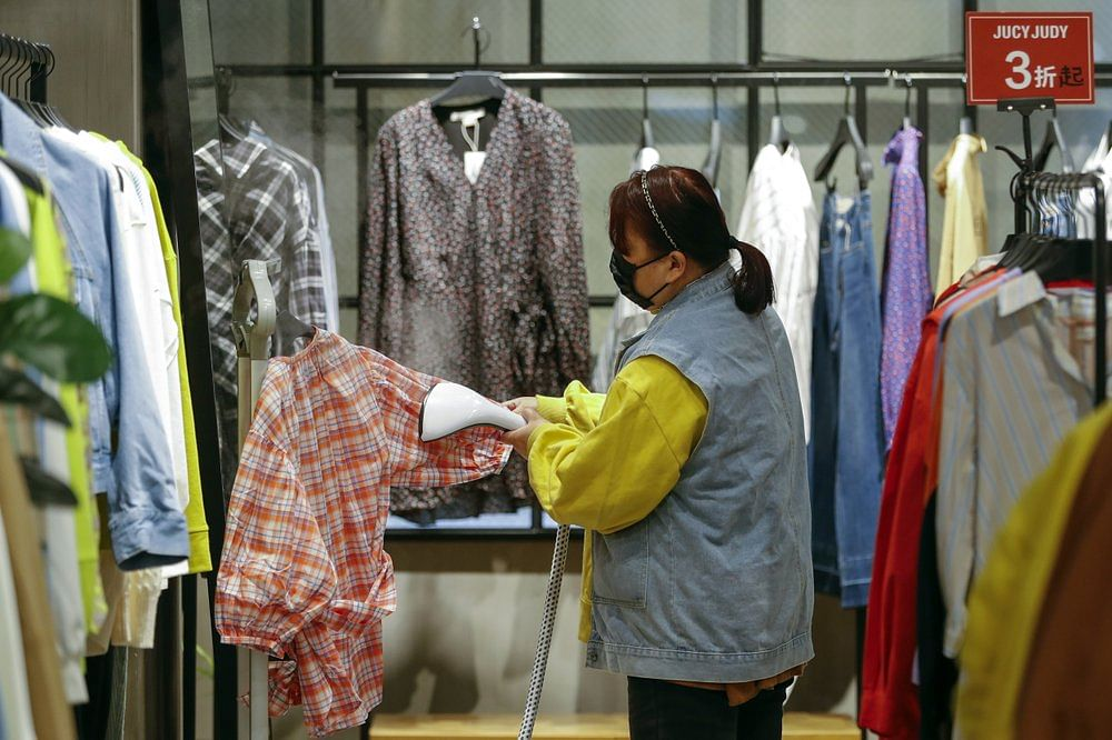 A worker wearing a protective face mask irons clothes at a re-opened shopping mall in in Wuhan in central China's Hubei province.
