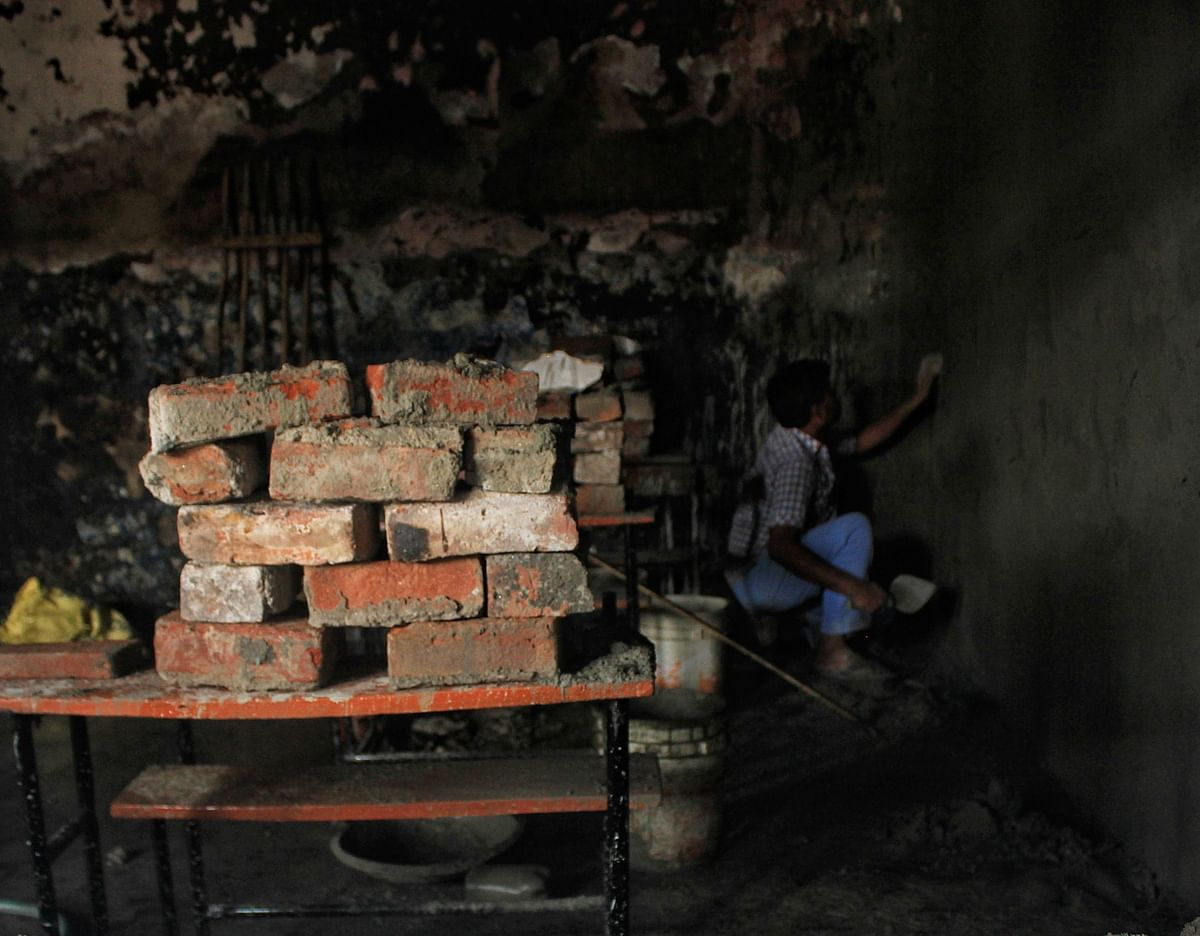 A worker plasters a damaged classroom wall of DRP Convent School.