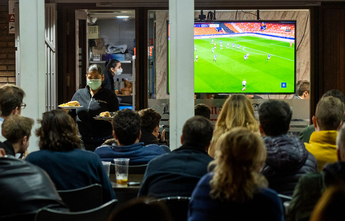 In this Tuesday March 10, 2020 filer, waiters wearing masks serve food and drink in a terrace outside Mestalla stadium during the Champions League round of 16 second leg soccer match between Valencia and Atalanta in Valencia, Spain.