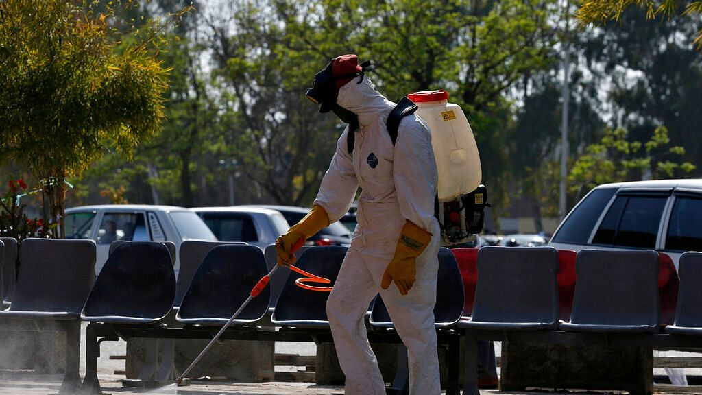 A worker wears protective gears disinfect an area as a precaution against the new coronavirus at the Pakistan Institute of Medical Sciences hospital in Islamabad, Pakistan, Tuesday, 17 March.