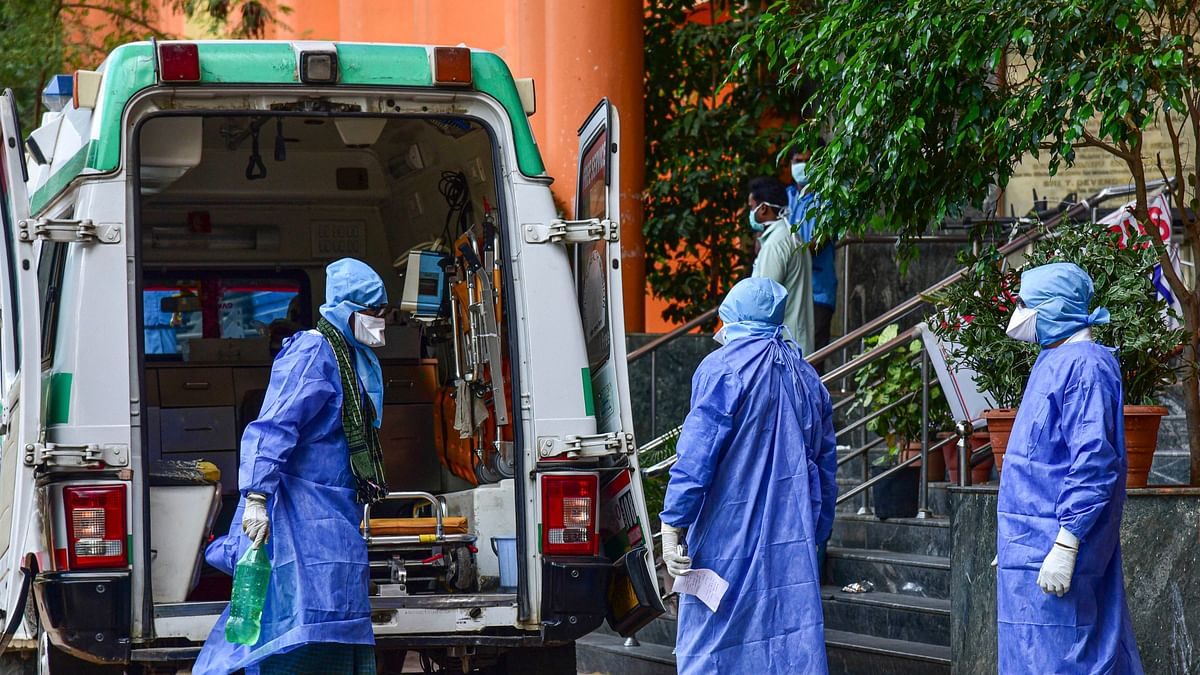 Medical workers attend to a suspected coronavirus patient (L), who travelled from Dubai, as he is moved to the isolation ward of Gandhi Hospital in Hyderabad.