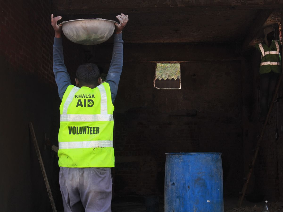 A worker carries concrete into Ashok Kumar's shop that is being rebuilt.