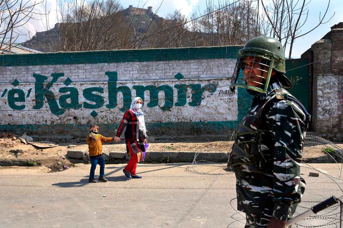 A Kashmiri woman along with her child walks past an Indian paramilitary soldier as restrictions are imposed on the movement of people after the first person in the region was tested positive for COVID-19 in Srinagar.