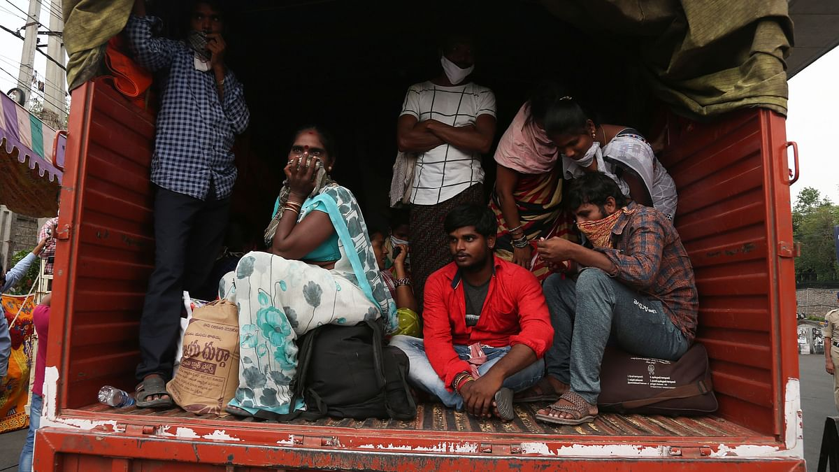 Indian migrants from Andhra Pradesh state, who were stopped while attempting to return to their native villages on foot, sit in a truck to be moved to a government facility during lockdown.