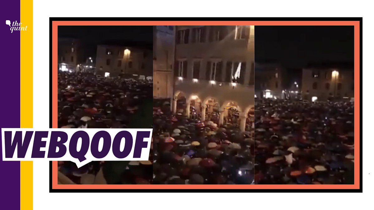 The video shows a huge crowd of people standing with umbrellas under heavy rain and singing 'Bella Ciao'.