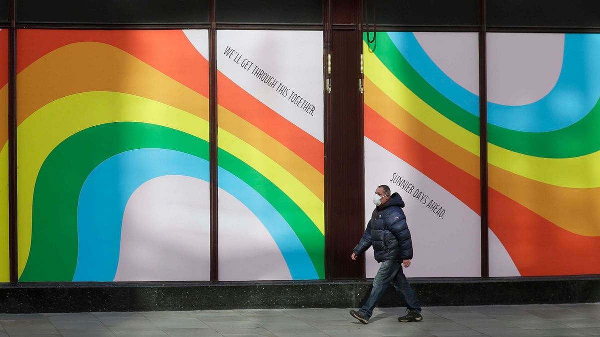 A man wearing a face mask to protect against catching the coronavirus walks past a window display of rainbows in the windows of the famous London department store Harrods in London, Tuesday, 31 March, 2020.