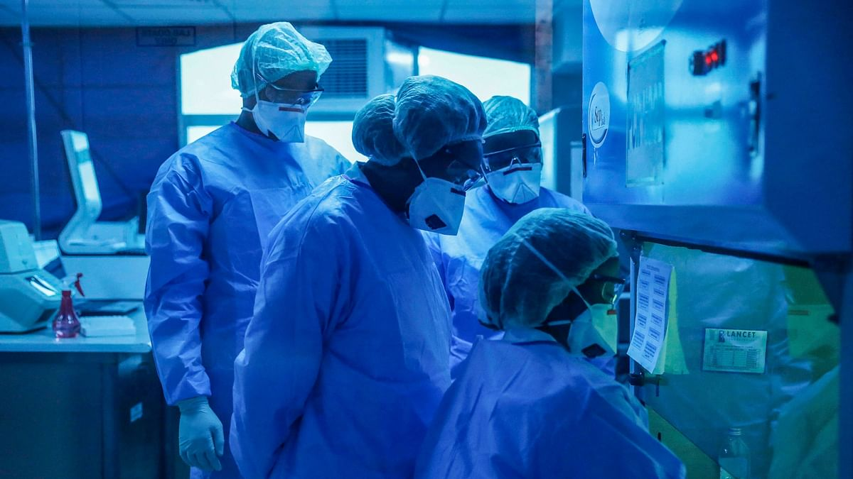 Nairobi: In this photo taken Sunday, 5 April, 2020, laboratory technicians, seen behind a blue-tinted window, work on testing patient samples for the new coronavirus that causes COVID-19, at the Pathologists Lancet Kenya laboratory in Nairobi, Kenya.