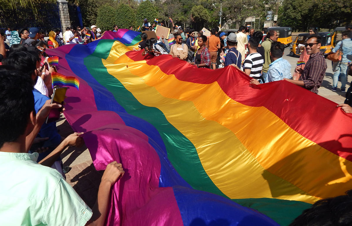 Indian LGBT activists holding a long rainbow flag