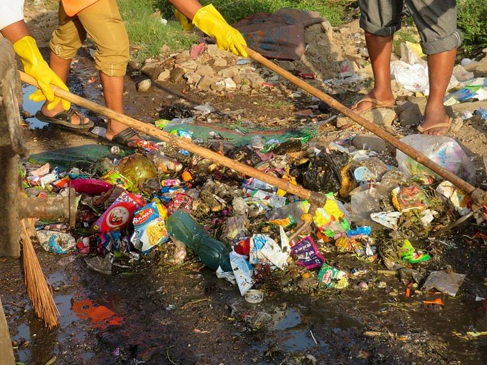 Sanitation workers in Mahul village, Chembur, Mumbai work with with minimal protection amidst possibly toxic garbage.