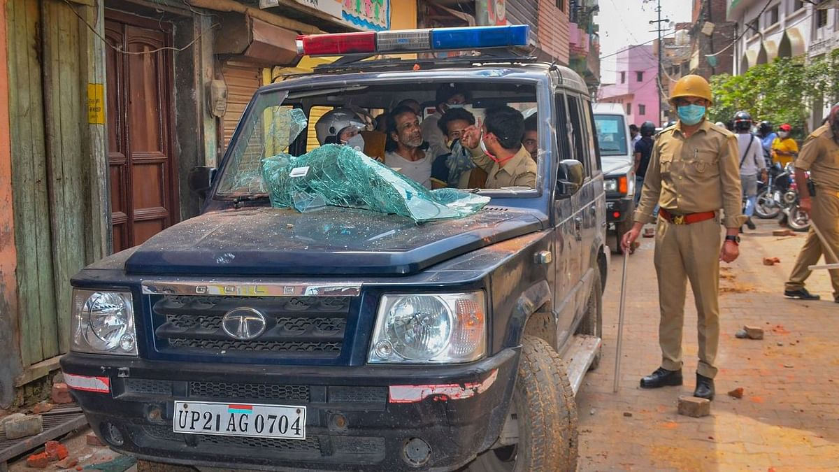 A team of medical personnel and police along with a patient sit inside a vandalised ambulance after a mob attacked their vehicle with stones.