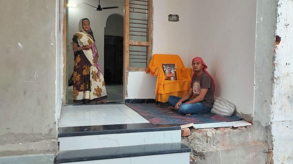 This is Ramesh's home, his son Rahul is sitting outside with his father's picture mounted on a chair. As is custom, he has shaved his head.