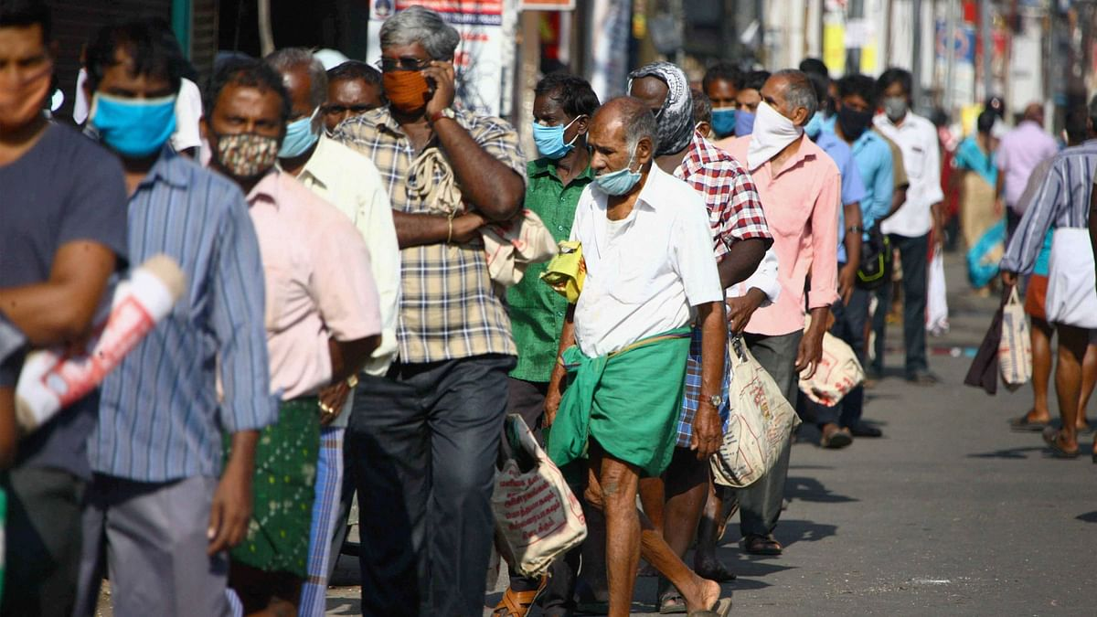 People stand in a queue to buy groceries and vegetables, during the  lockdown, in Coimbatore, Thursday.